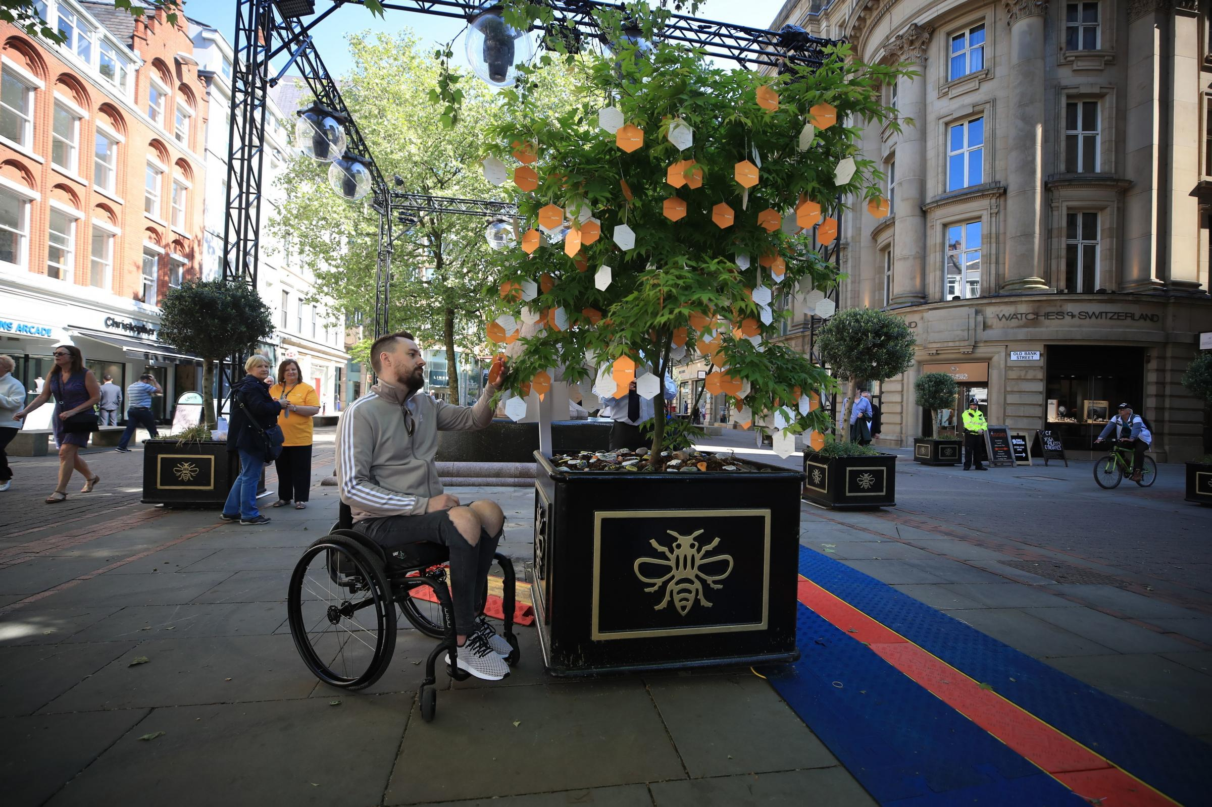 Martin Hibbert, who suffered life-changing injuries in the Manchester terror attack, reads messages left on a 'Tree of Hope' in St Ann's Square, Manchester