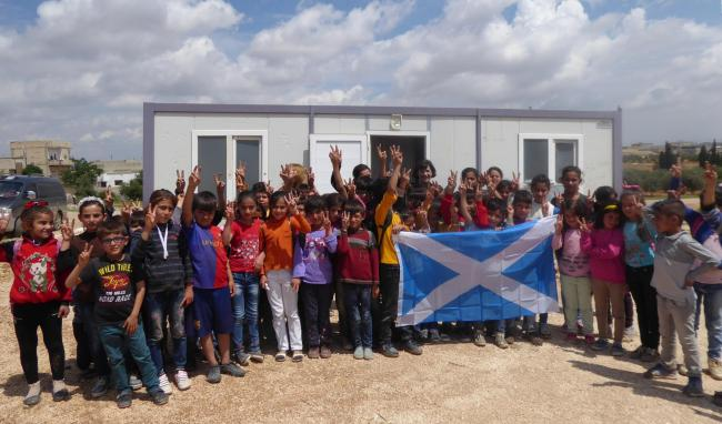 Primary school children outside their temporary classroom in Kobanê. Scottish Solidarity with Kurdistan is raising funds to build a proper school on this site