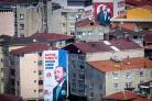 An election poster showing the portrait of Turkey's President Recep Tayyip Erdogan is seen in front of a portait of Mustafa Kemal Ataturk