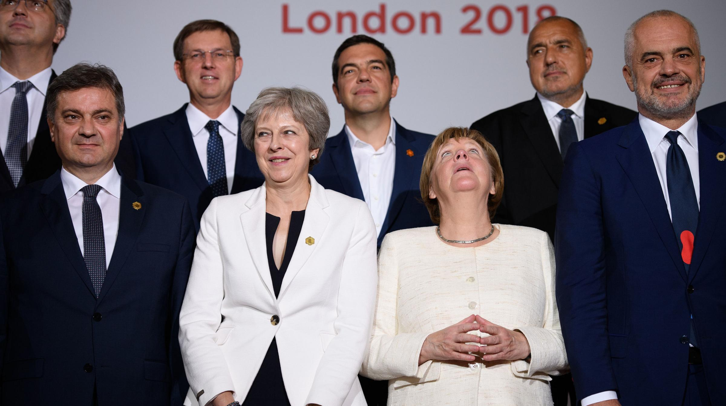 Theresa May looks uncomfortable as she lines up with Angela Merkel and other leaders during the second day of the Western Balkans summit in London