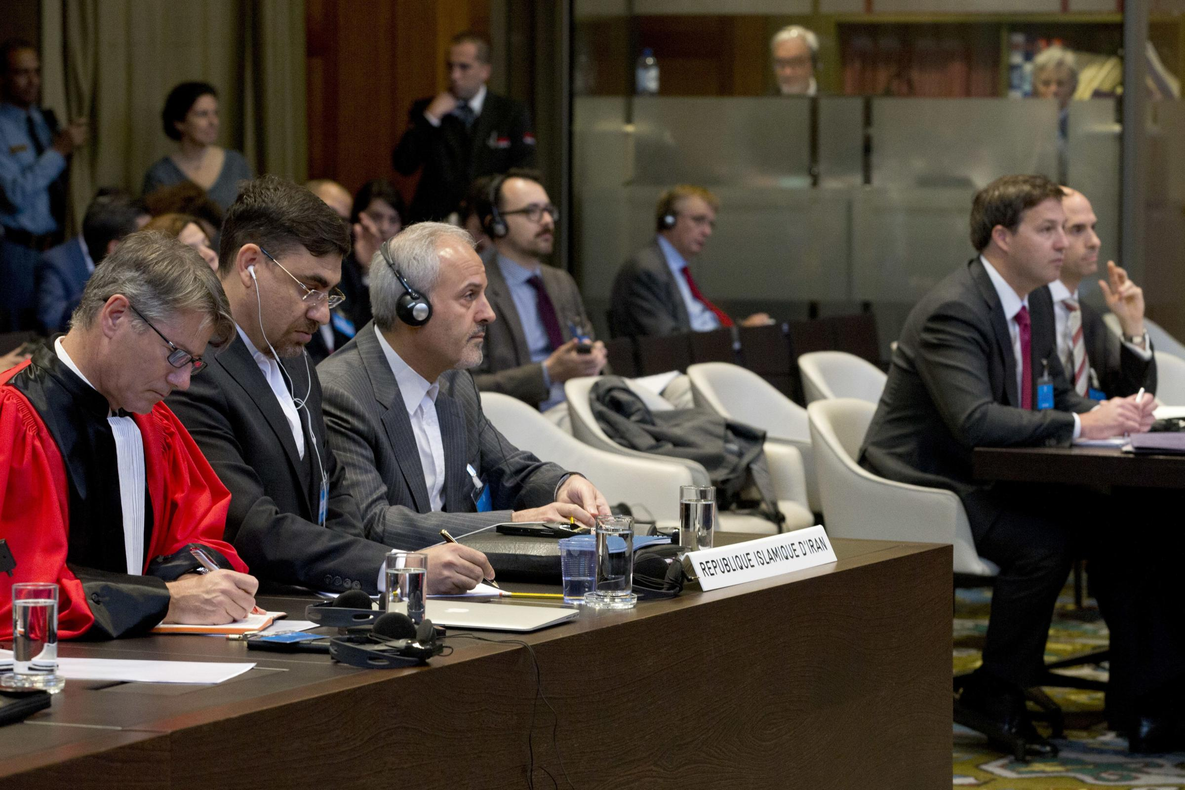 Mohammed Zahedin Labbaf, third left, agent for the Islamic Republic of Iran, and the U.S. delegation, right, heard the ruling