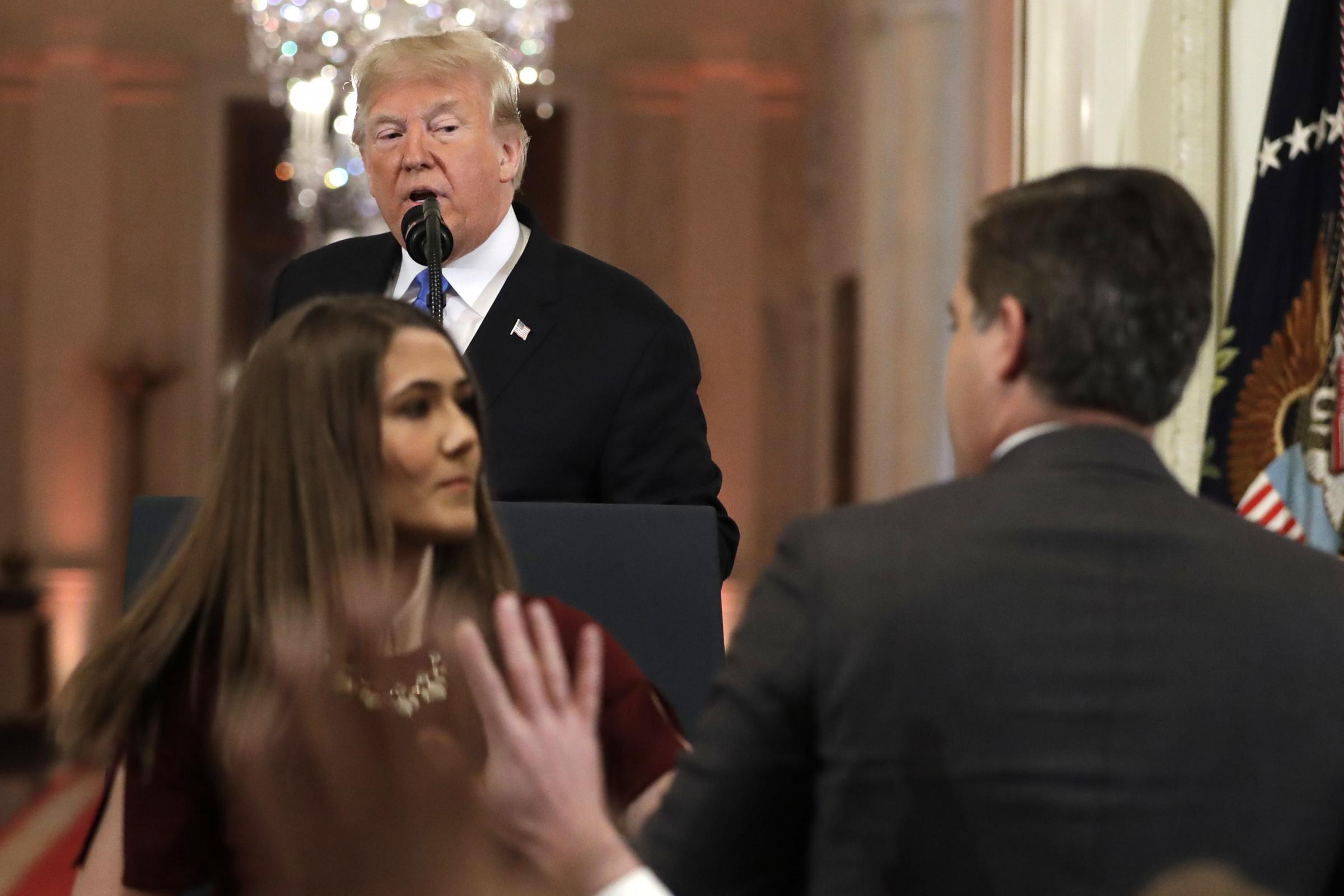 President Donald Trump looks on as a White House aide takes away a microphone from CNN journalist Jim Acosta