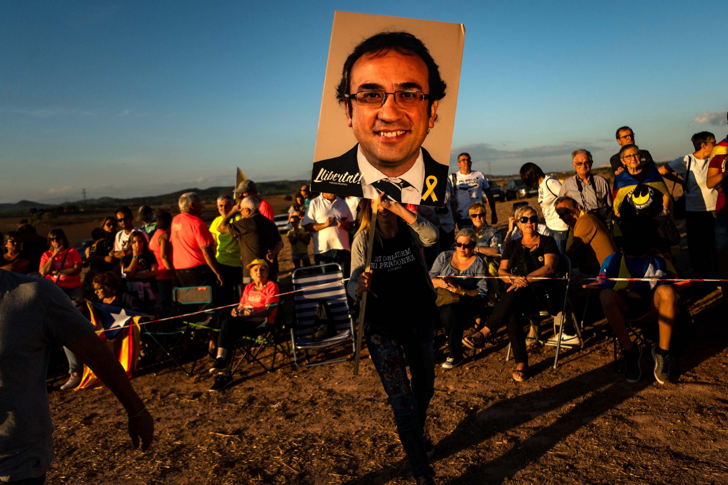 A Catalan independence supporter holds a portraits of jailed separatist leader Jordi Turill, who remains on hunger strike