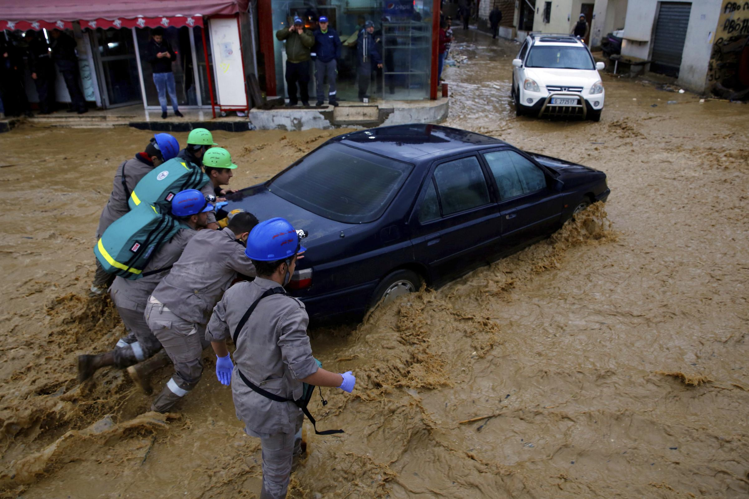 Civil Defense workers struggle to push a stranded car on a street in Beirut, Lebanon