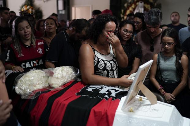 The National: Marilia Barros da Silva, grieves over the coffin containing the remains of her son, the young soccer player Arthur Vinicius, one of the victims of a fire at a Brazilian football academy