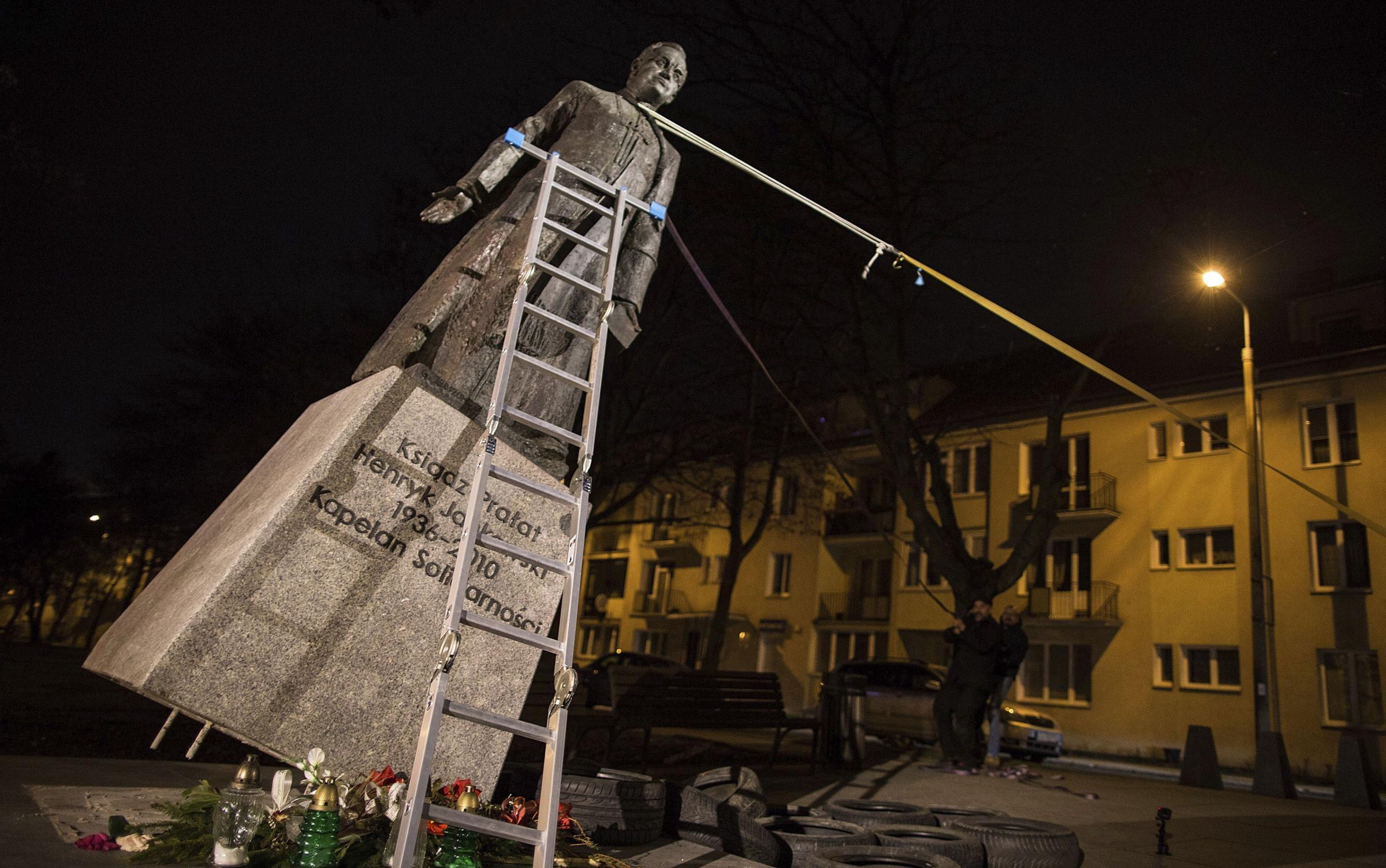 Activists in Poland pull down a statue of a prominent deceased priest, Father Henryk Jankowski, who allegedly abused minors sexually, in Gdansk, Poland