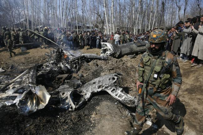 An Indian army solider walks past the wreckage of an Indian aircraft after it crashed in the Budgam area