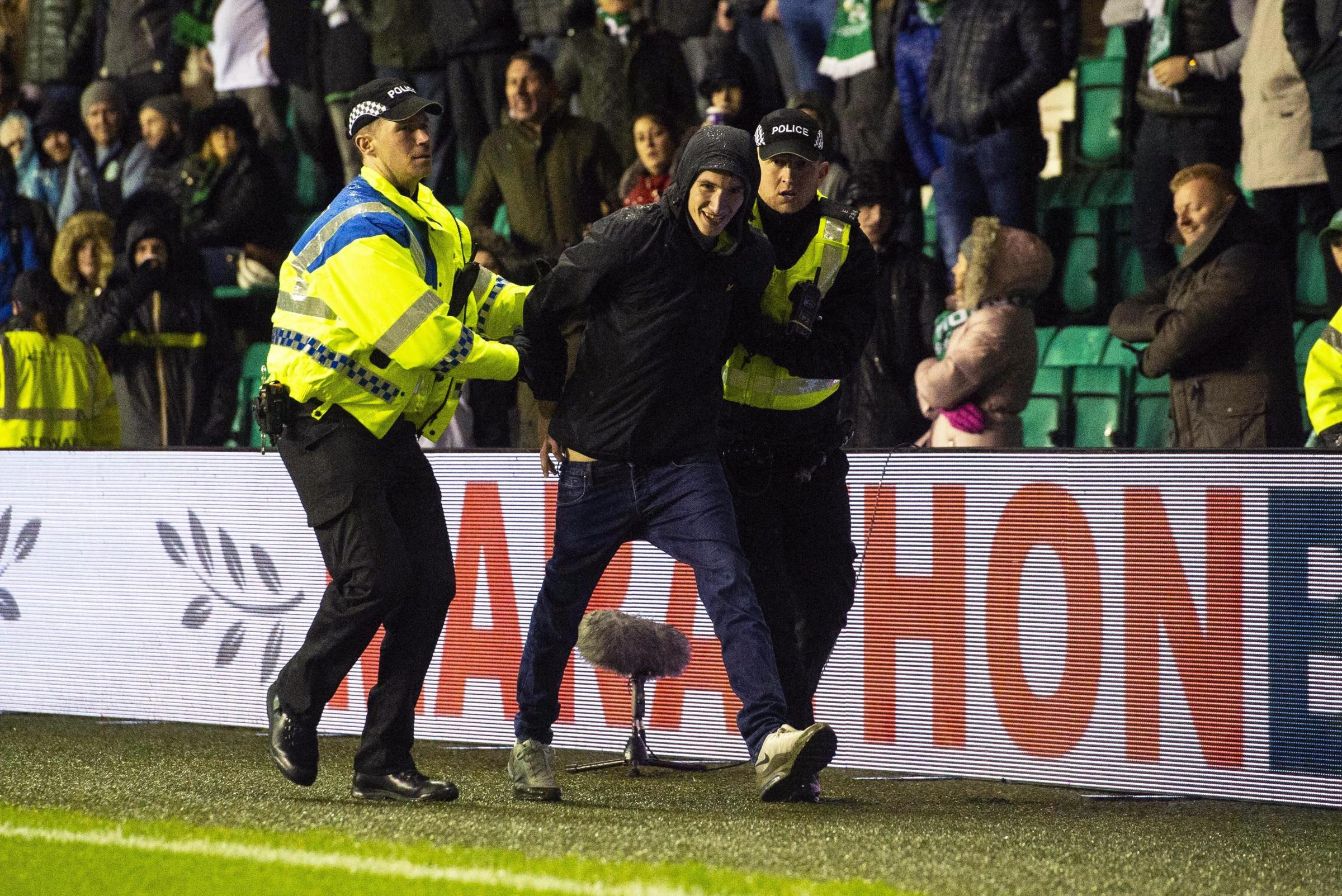 A Hibs fan is led away by police after running on to the park to confront James Tavernier