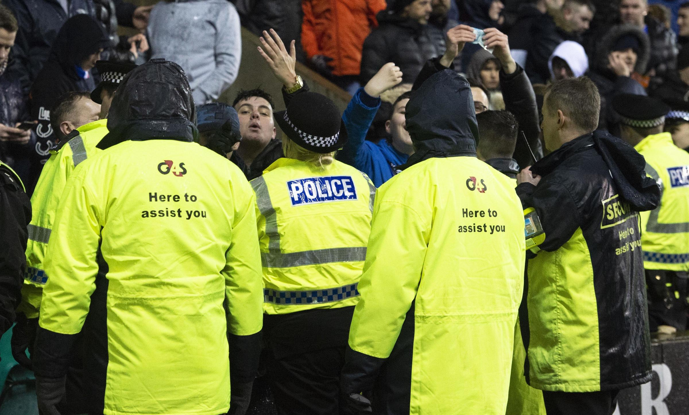 Rangers fans are held back by police after James Tavernier is confronted by a Hibs fan on the pitch at Easter Road on Friday night.