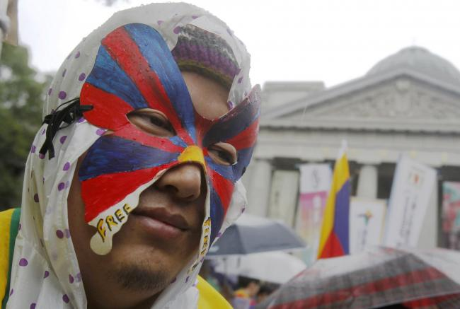 A Tibetan living in Taiwan wears a mask painted in the colour of the Tibet national flag