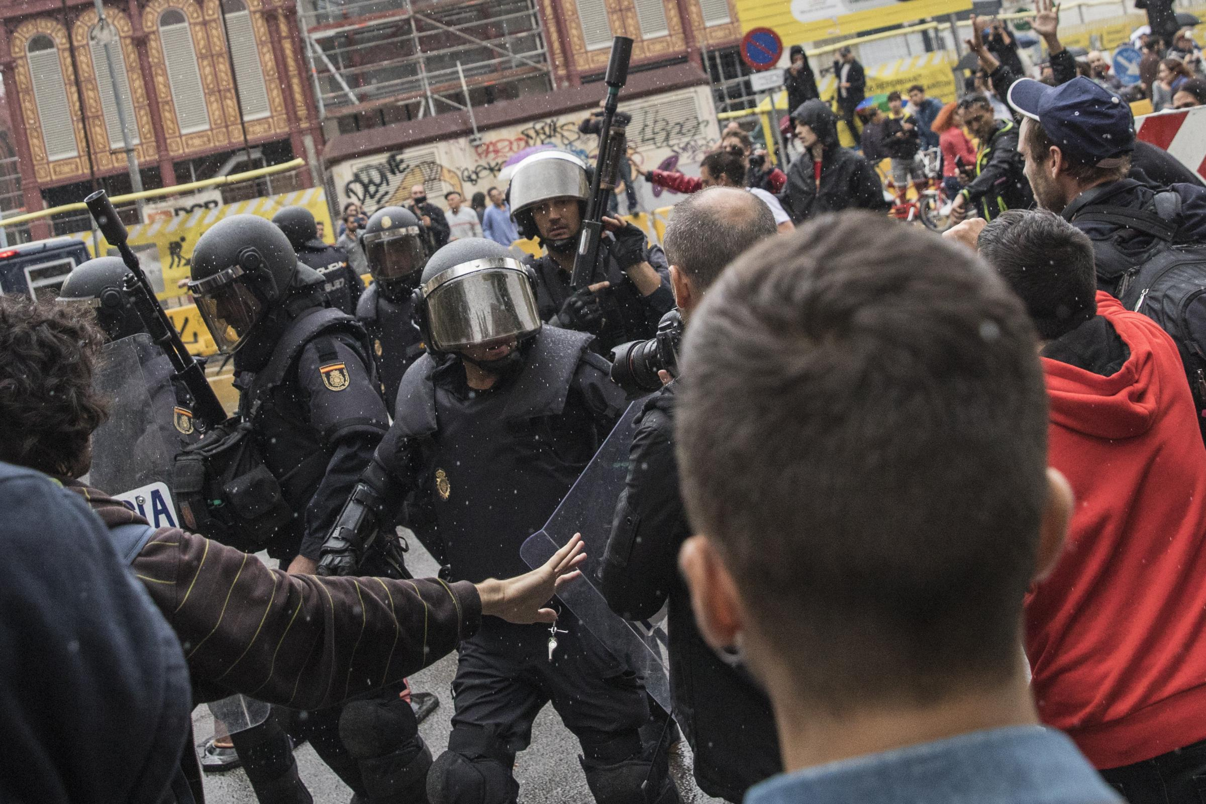 Spanish National Police clash with voters outside a polling station in Barcelona on October 1, 2017